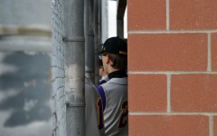 While getting ready in the dugout, Jacob Hughes, 9, watches the game and cheers on the Broncos. The freshmen team faced off against the Shawnee Mission East Lancers but came up short with a final score of 10-4, Mar. 24. (Photo by J. Barnett)