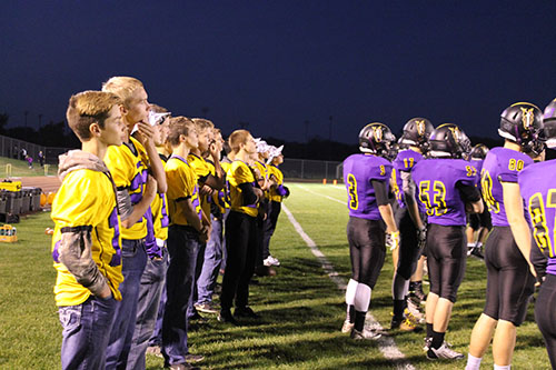 The JV and freshman football teams watch the varsity game behind the players. The boys watched from the sideline during the game against the Eudora Cardinals (Photo by P. Swanda).