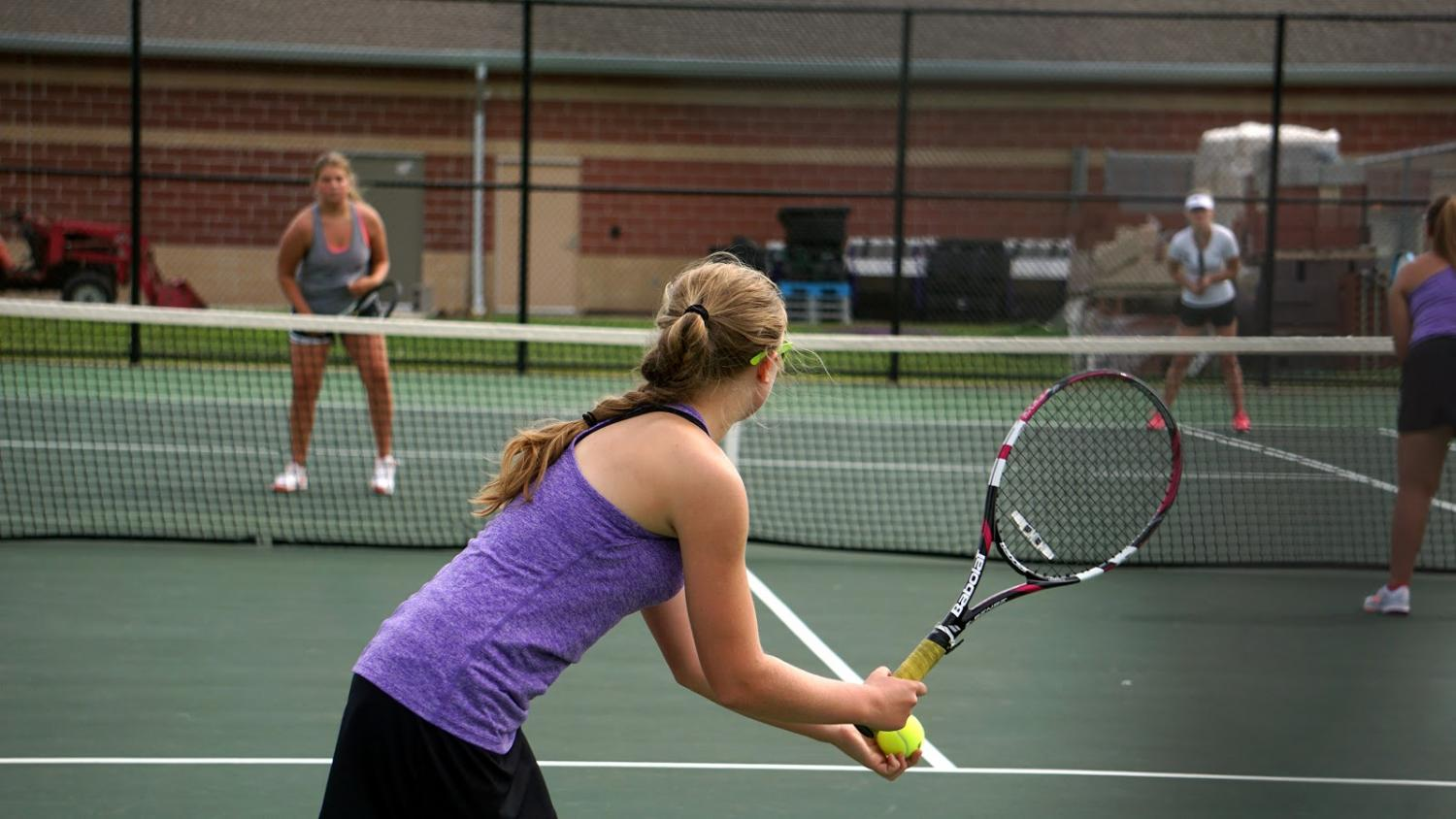 During the first tennis match of the season, KayLee Mitchell, 12, sets up for a serve. The Lady Broncos defeated Lansing in both varsity and Jr. Varsity matches. (photo by J. Barnett)
