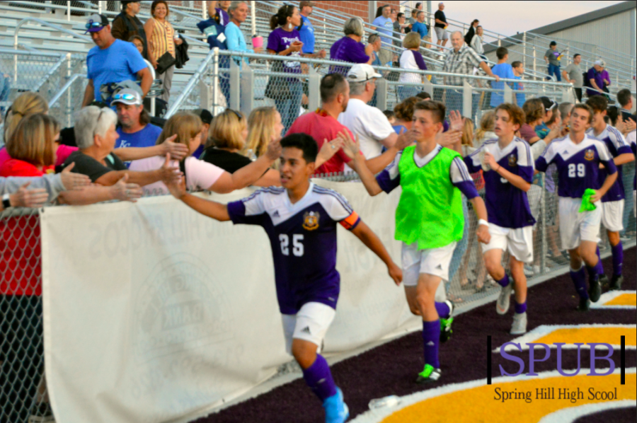 Following the varsity game, Josh Santos, team captain, 12, leads the varsity down the field to give high fives to the fans lined up along the fence. (Photo by B. Gulley)