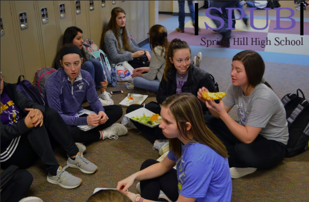 A group of Sophomore girls hang out and eat lunch. Some are doing their homework, others talking and having fun (photo by JClark).