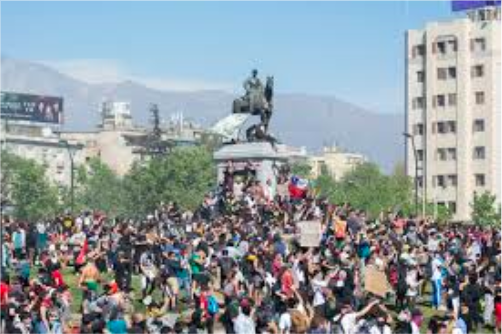 Chilean citizens protesting in the streets about the political unrest. The APEC and UN summits were canceled because of the massive amounts of protest.