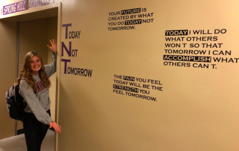 "Varsity player, Avery Anderson, 12, shows off the locker room wall decorated for the upcoming basketball season. Their motto for this year is ""TNT,"" which stands for ""Today Not Tomorrow"" (Photo submitted by Clay Frigon)."