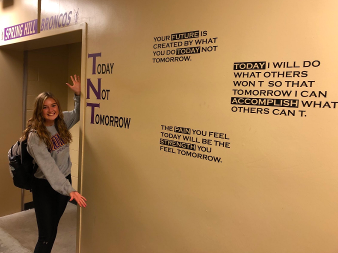 """Varsity player, Avery Anderson, 12, shows off the locker room wall decorated for the upcoming basketball season. Their motto for this year is """"TNT,"""" which stands for """"Today Not Tomorrow"""" (Photo submitted by Clay Frigon)."""