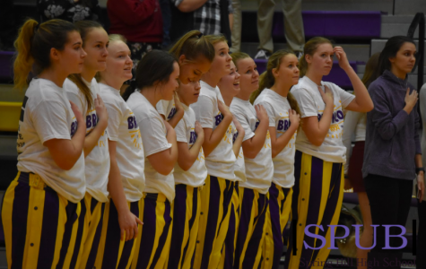 The varsity girls basketball team as they stand for the National Anthem. The girls went on to beat Atchison in their first game of the season (photo by A Frigon).