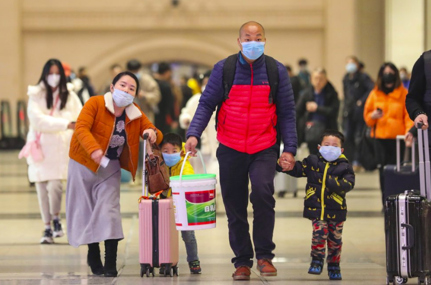 Family travelers walk through  Hankou Railway Station in Wuhan in southern China's Hubei province with luggage. Concerns have sparked all around that the virus will spread with large travel season coming up (Photo curtesy of Chinatopix via AP).