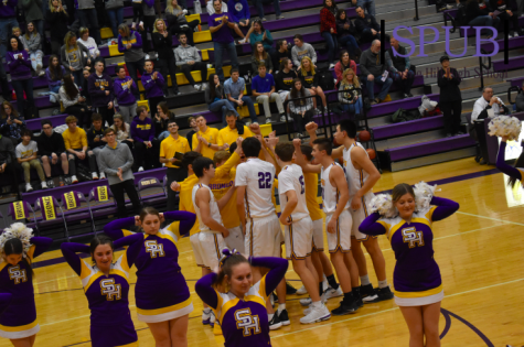 The cheerleaders lead the crowd in Fight Song before the varsity boys basketball game starts. The boys played on Dec. 13 and lost to Lansing High School (Photo by MSutton)