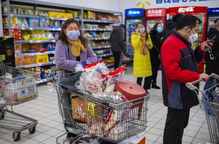 At a grocery store, in Wuhan in central China's Hubei Province, shoppers wear face masks to protect themselves from the Cornavirus, on Jan. 22. As the virus has swept through the city of 11 million chinese officials say that the U.S.' reaction hasn't been helpful (Photo courtesy of AP Photo and Arek Rataj).