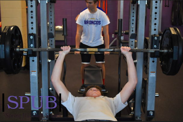 On Nov. 21, in their Weights class Zack Philips, 10, bench presses while Tristan Taylor, 10, sets up his weights. They are hoping to maintain their health by doing this one small thing (Photo by KRios).