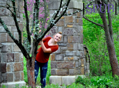 On April 24, Alynna Mattox, 9, felt creative to pose behind this tree during a field trip to the arboretum. Mattox is preparing to go on a trip over spring break (Photo by AMarney).
