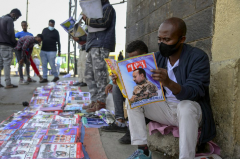 On Nov. 7, an Ethiopian citizen reads news about the ongoing conflict in Ethiopia. Since then, hundreds of thousands of refugees have fled the country, seeking refuge in Sudan (photo courtesy AP News).