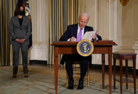 President Joe Biden signs executive orders in the state dining room on Jan. 26 as Vice President, Kamala Harris, stands to his left. As Biden finishes his first week in office by digging deeper into several issues many americans care about (Photo courtesy of AP photo and Evan Vucci).
