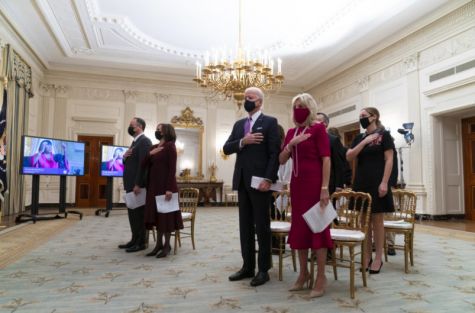 Vice President Kamala Harris, and President Joe Biden stand with their respective spouses for the playing of the national anthem during a virtual prayer service on Jan. 20. This was Biden