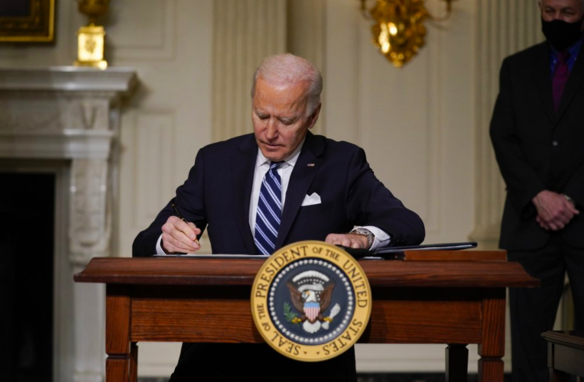 In the state dining room, on Jan. 27, President Joe Biden signs an executive order on climate change. Over his first week in office Biden has taken a lot of executive action (Photo courtesy of AP Photo/Evan Vucci).