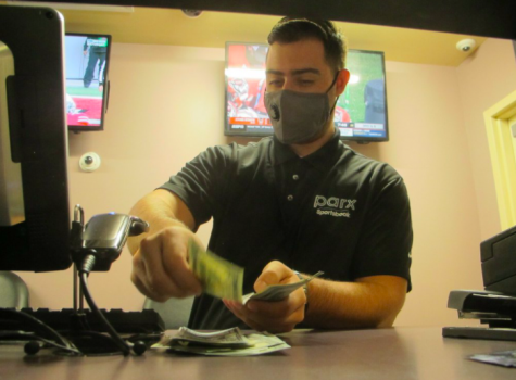 A clerk at the Freehold Raceway in Freehold, N.J. counted money in the sports betting lounge. Due to the ongoing pandemic, and the resulting financial situations of many Americans, betting is supposed to fall dramatically this year (photo courtesy AP News).