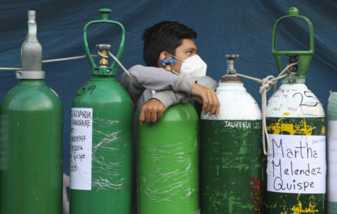 A young man waits for an oxygen refill shop to open in Peru. Nations in South America and Africa  have been experiencing mass shortages of oxygen due to the COVID-19 pandemic (photo courtesy AP News).