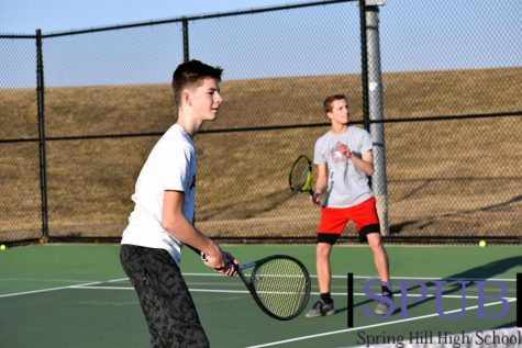 During practice, Joey Reinhart, 9, and Keagan Sinclair, 10, work on improving their volley skills while up at the service line (Photo by I. Williams).