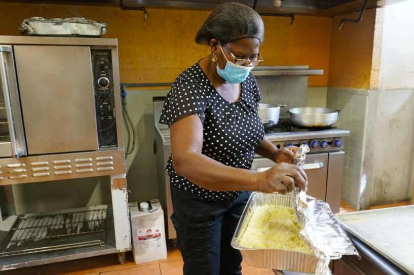 Doramise Moreau, a part-time janitor at a technical school in Miami, has been cooking 1,000 meals a week since the pandemic started. Working out of a local church, she uses her talents to feed those in need (photo courtesy AP News).