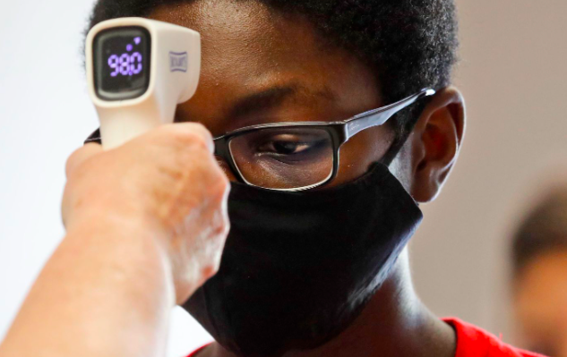 A student wearing a mask has his temperature checked by a teacher before entering a school in Texas in July (photo courtesy AP Photo/LM Otero).
