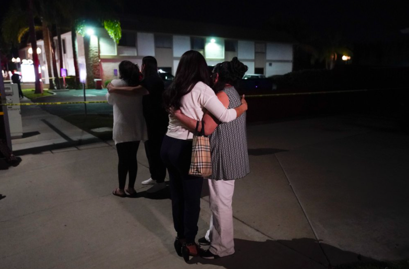 Two people comfort each other outside an office building where four people were killed on Wednesday (photo courtesy AP News).