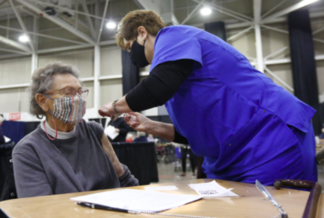 Tami Morrison, right, is giving Lisetta White her first COVID-19 vaccination (photo courtesy AP news).