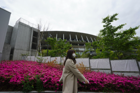 A woman walks past the Japan National Stadium, where all the festivities of the Olympics will take place (photo courtesy AP News).